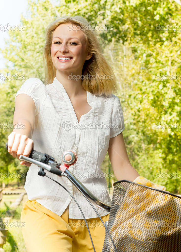 Portrait of an happy smiling young woman riding a bicycle in the park.Looking at camera. — Foto Stock #13312779