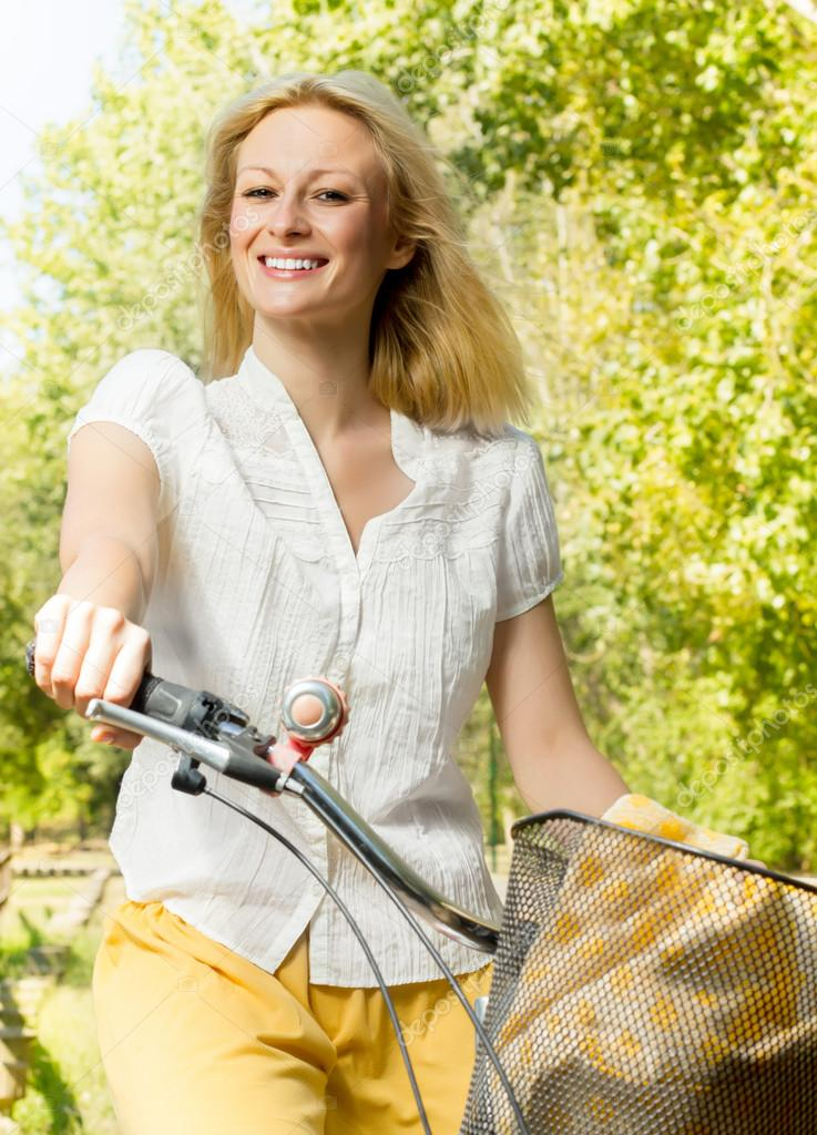 Portrait of an happy smiling young woman riding a bicycle in the park.Looking at camera. — 图库照片 #13312779
