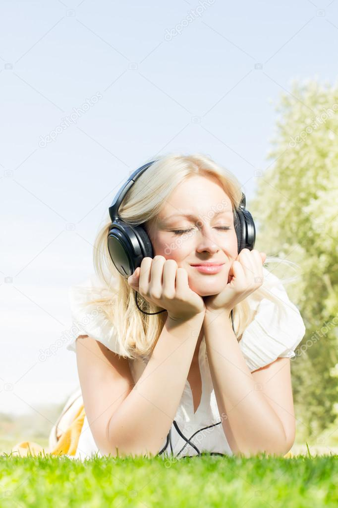 Happiness blonde woman with headphones relaxing on green grass in the park. — Stock Photo #13313989