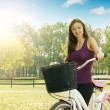 Stock Photo: Cheerful girl with a bicycle