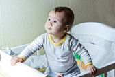 Cute baby girl in her cot — Stock Photo