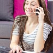 Young woman speaking by phone and using laptop — Stock Photo
