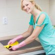 Beautiful housewife cleaning in the kitchen — Stock Photo #27150475