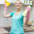 Happy housewife cleaning in the kitchen — Stock Photo