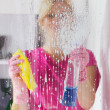 Stock Photo: Housewife with protective glove washing window glass