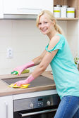 Beautiful housewife cleaning in the kitchen — Stock Photo