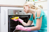 Young woman cleaning oven in the kitchen — Stock Photo
