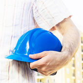Construction worker holding blue hard hat — Stockfoto
