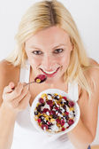 Portrait of lovely blonde woman eating cereals with fruit at breakfast — Stock Photo