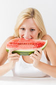 Smiling young woman eating fresh watermelon — Stock Photo