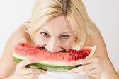 Happy young woman eating fresh watermelon — Stock Photo