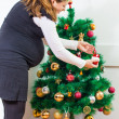 Happy pregnant woman decorate a Christmas tree — Stock Photo