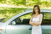 Young woman showing new car — Stock Photo