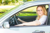 Happy young woman driving a car — Stockfoto