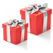 Two red gift boxes with silver ribbon on white background. — Stock Photo