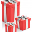 Three red gift boxes with silver ribbon on white background. — Stock Photo