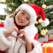 Happy young girl smiling near the Christmas tree. — Stock Photo