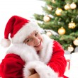 Foto Stock: Happy young girl smiling with gift box near Christmas tree.