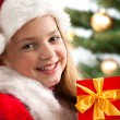 Girl smiling with gift box near the Christmas tree. — Stock Photo