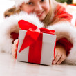 Happy young girl smiling with gift box near the Christmas tree. — Stock Photo