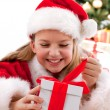 Happy young girl smiling with gift box near the Christmas tree. — Stock Photo #16029997