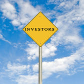 Road sign to investors — Stock Photo