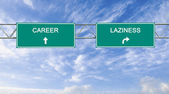 Road sign to lazinessl and career — Stock Photo