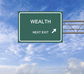 Road sign to wealth — Stock Photo