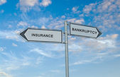 Road sign to insurance and bankruptcy — Stock Photo