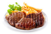 Plate of grilled meat with frieis — Stock Photo