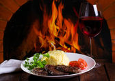 Grilled meat and glass of wine — Stock Photo