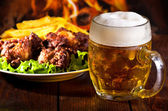 Beer and grilled chicken wings — Stock Photo