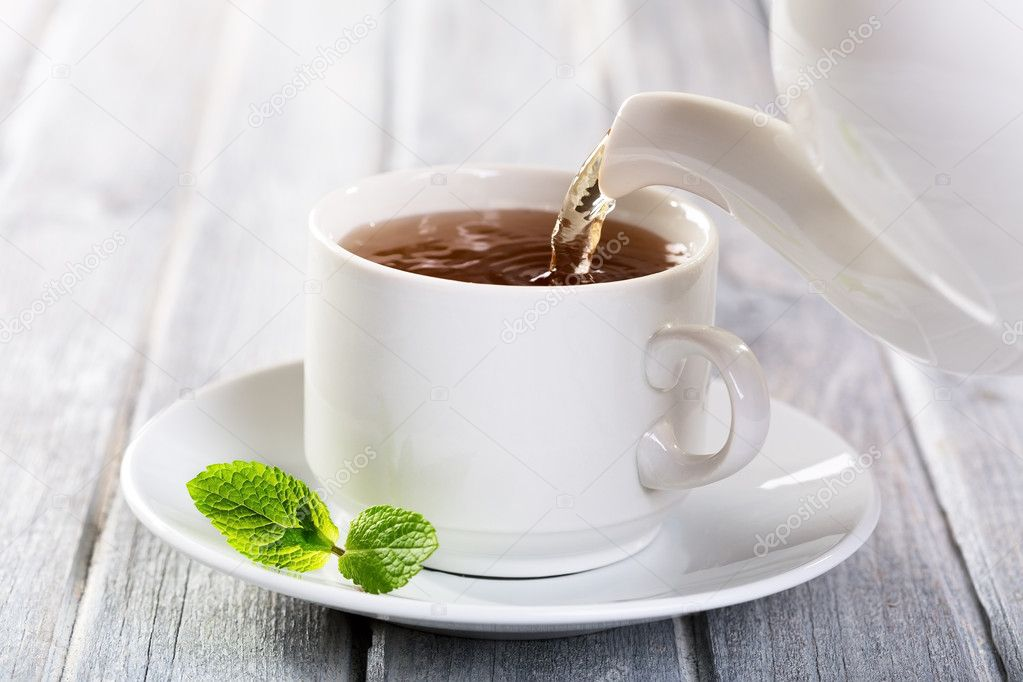 Pouring tea into cup of tea — Stock Photo #13517469
