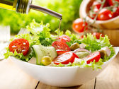 Olive oil pouring over salad — Stock Photo