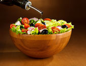 Oil pouring into bowl of vegetable salad — Stock Photo