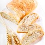 Sliced ciabatta bread with wheat ears — Stock Photo #38714785