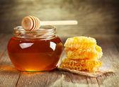 Jar of honey with honeycomb — Stock Photo