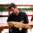 Fisherman with carp — Stock Photo