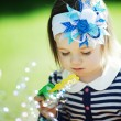 Little funny girl plays with bubbles — Stock Photo #17214653