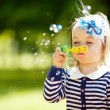 Little girl plays with bubbles — Stock Photo