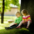 Cute boy and girl reading a book — Stockfoto