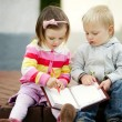 Boy and girl writing to notebook — Stock Photo