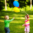 Stock Photo: Girl and boy playing with balloons in park