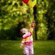 Little funny girl plays with balloons in park — Stock Photo #17214703