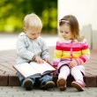Cute boy and girl reading a book — 图库照片
