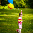 Little funny girl plays with balloons in park — Stock Photo #17214729