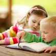 Foto Stock: Cute boy and girl reading a book