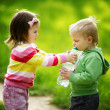 Boy and girl sharing bottle of water — Stockfoto