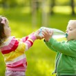 Stockfoto: Girl helps the boy to keep a bottle