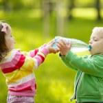 ragazza aiuta il ragazzo a tenere una bottiglia — Foto Stock